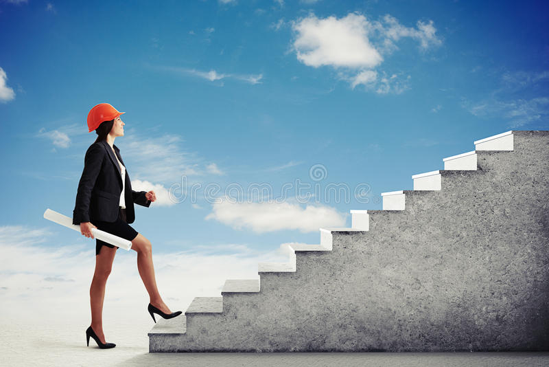 La donna graziosa scala le scale concrete nel cielo immagini stock