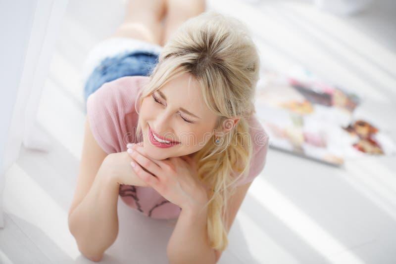 La donna graziosa si trova su un pavimento leggero con i suoi occhi chiusi immagine stock