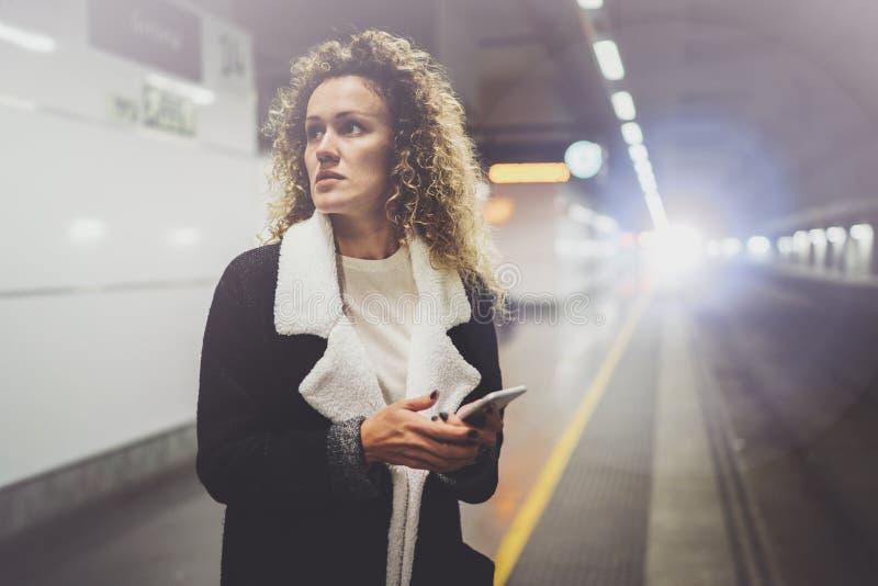 La donna graziosa sopra permuta il transito facendo uso dello smartphone mentre sta nella stazione ferroviaria Ragazza attraente  fotografia stock
