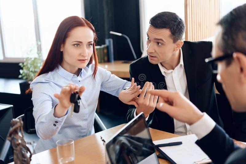 La donna graziosa sta tenendo sulle chiavi del dito che si siedono accanto all'uomo adulto nell'ufficio del ` s dell'avvocato fotografia stock libera da diritti