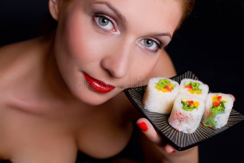 La donna graziosa sta tenendo una zolla con alimento giapponese immagine stock