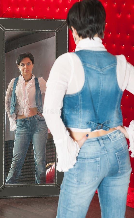 La donna guarda nello specchio immagini stock