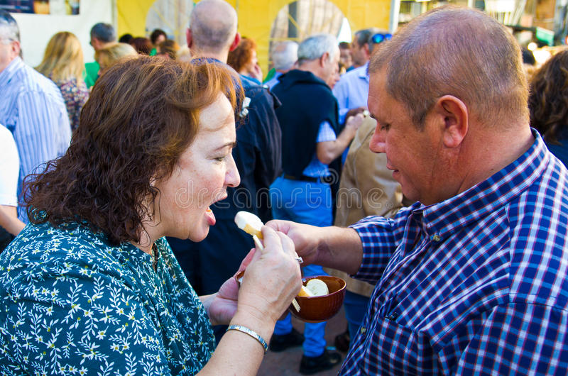 La donna ha aperto la sua bocca L'uomo sta alimentando una fonduta di formaggio della donna con un cucchiaio Il bianco ha fuso gl fotografia stock libera da diritti