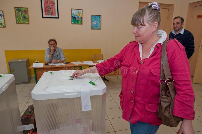 La donna ha messo il voto di elezione con i candidati per il sindaco di Mosco fotografia stock
