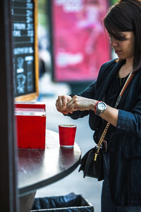 La donna ha messo lo zucchero in tazza di caffè di carta rossa fotografia stock