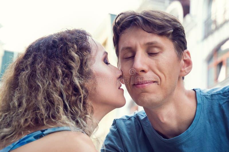 La donna ha premuto il suo naso alla guancia del suo amante L'uomo ha chiuso vago i suoi occhi Costruzioni antiche sui precedenti fotografie stock