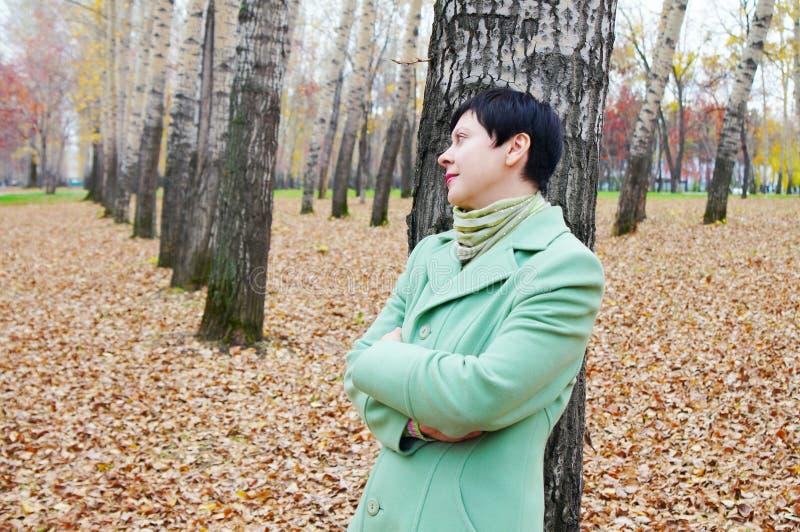 La donna ha un resto nella sosta di autunno immagini stock