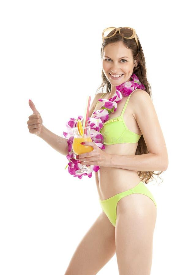 La donna hawaiana sorridente felice con il cocktail arancio mostra il pollice su immagini stock libere da diritti