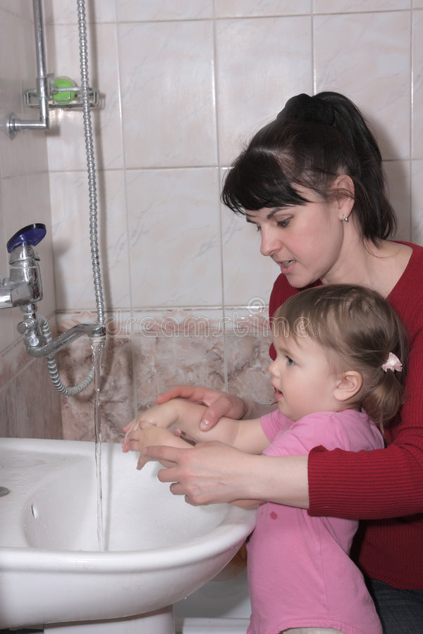 La donna impara la ragazza per lavarsi le mani immagine stock