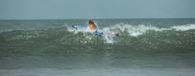 La donna impara praticare il surfing fotografia stock libera da diritti