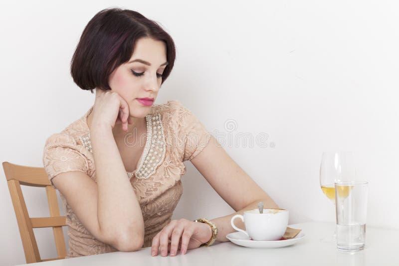 La donna impaziente esamina il suo orologio fotografia stock libera da diritti