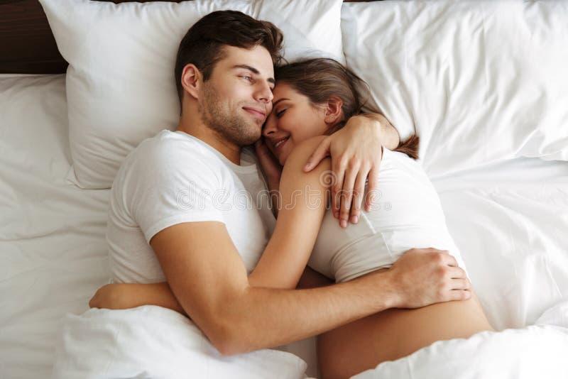 La donna incinta allegra si trova a letto con il marito immagini stock