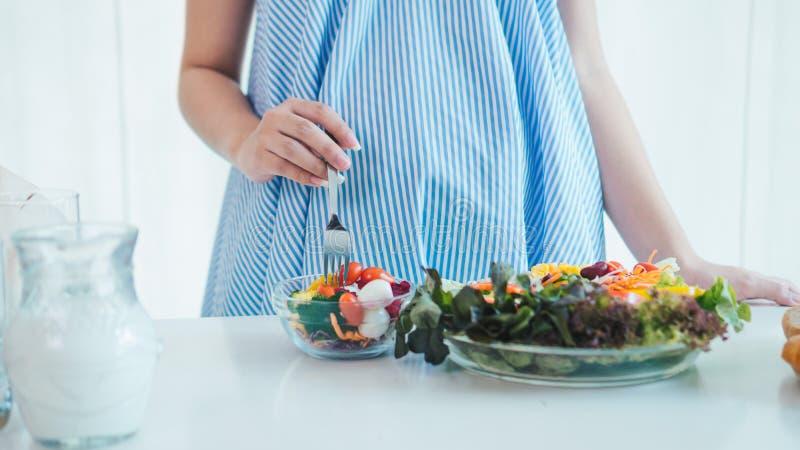 La donna incinta asiatica sta mangiando l'insalata immagini stock libere da diritti
