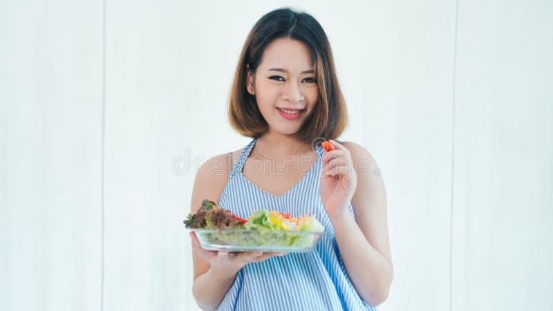 La donna incinta asiatica sta mangiando l'insalata fotografia stock