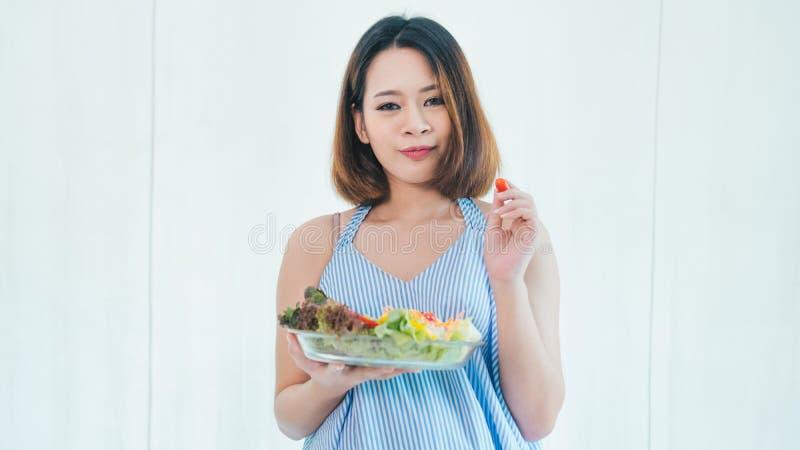 La donna incinta asiatica sta mangiando l'insalata fotografia stock libera da diritti