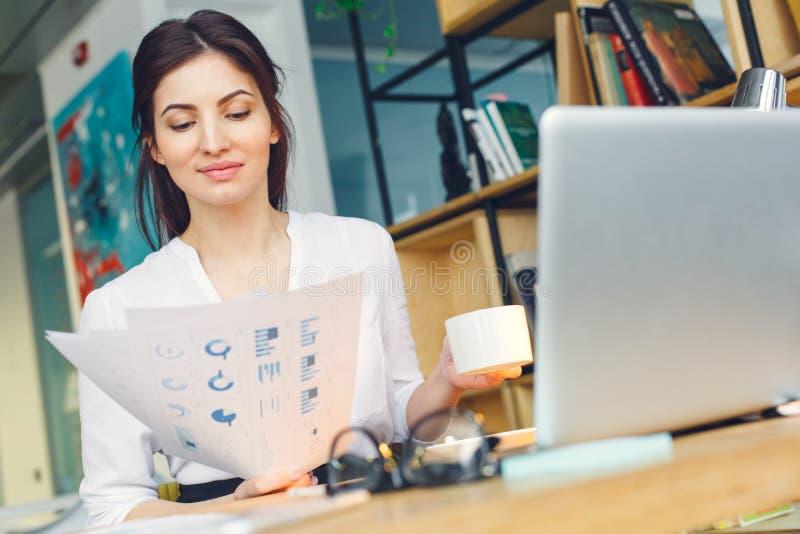 La donna incinta di affari che lavora alla lettura di seduta di maternità dell'ufficio documenta il primo piano fotografia stock