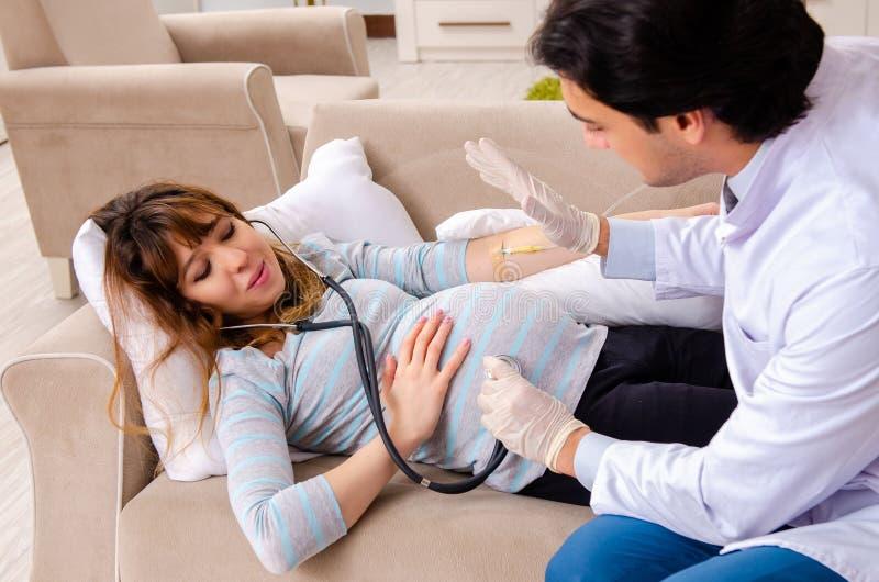 La donna incinta di visita di giovane medico bello a casa fotografia stock