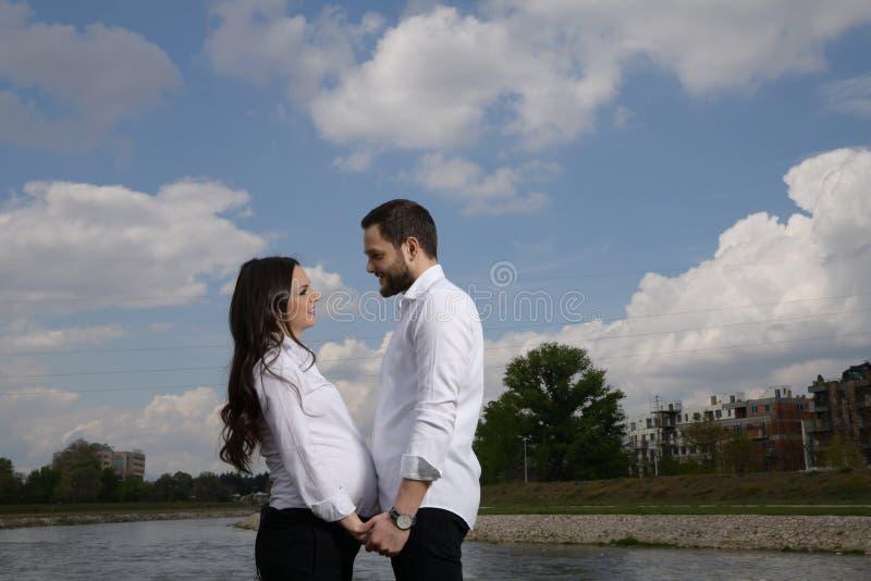 La donna incinta e l'uomo sono abbraccianti e posanti al parco dell'estate fotografia stock libera da diritti