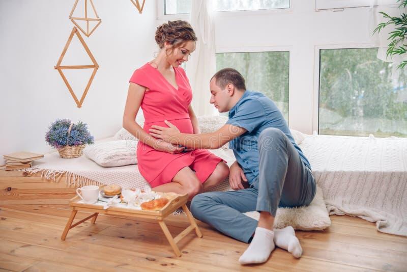 La donna incinta felice con il suo marito è tenente ed ascoltante il bambino in pancia e mettente sul pavimento del ` s del salon fotografie stock libere da diritti