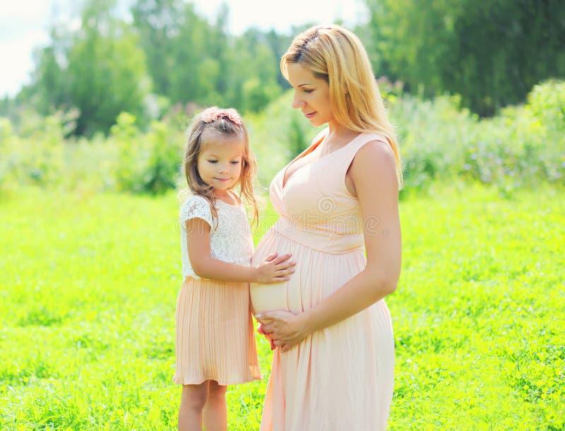 La donna incinta felice, figlia del piccolo bambino tocca la madre della pancia immagini stock libere da diritti