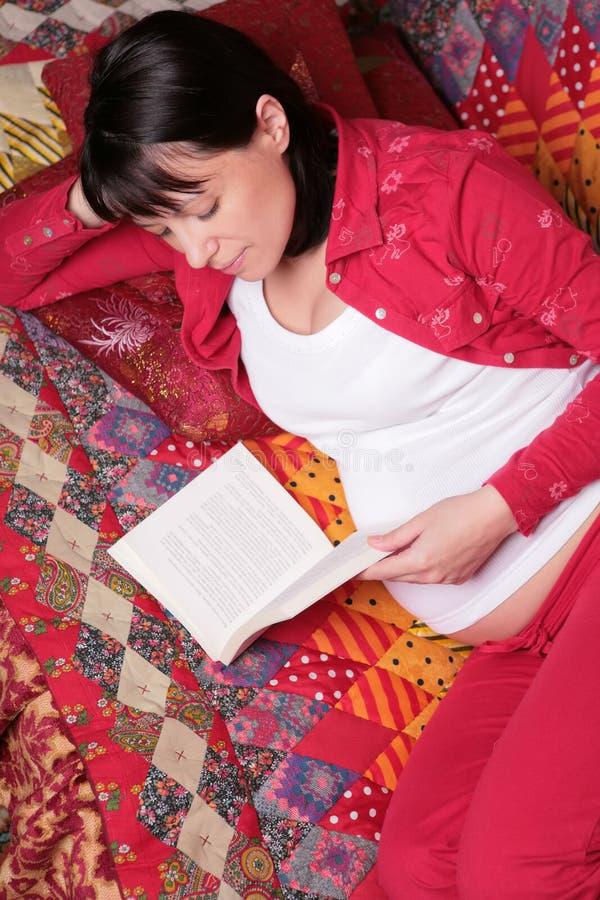 La donna incinta legge il libro immagini stock libere da diritti