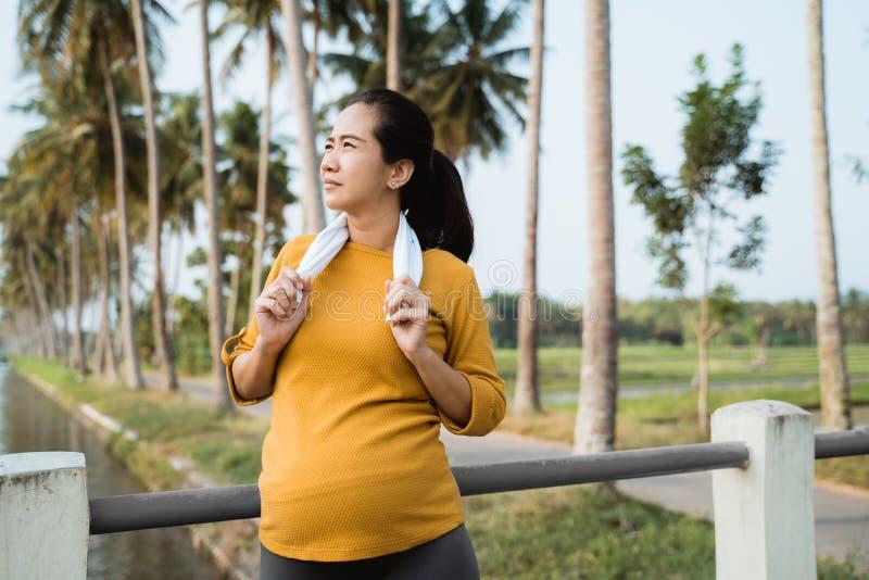 La donna incinta prende una rottura dopo l'esercitazione all'aperto immagine stock