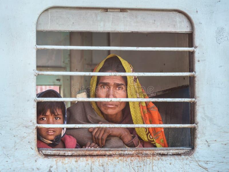 La donna indiana con il bambino sta sedendosi in treno e sta guardando attraverso la finestra del treno in Sambhar Il Ragiastan L immagini stock