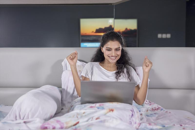 La donna indiana felice utilizza un computer portatile sul letto fotografia stock
