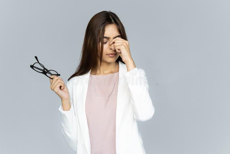 La donna indiana stanca di affari ritiene i vetri della tenuta dell'astenopia isolati su fondo fotografia stock