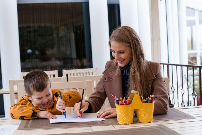 La donna insegna al ragazzo a disegnare con le matite colorate immagini stock libere da diritti