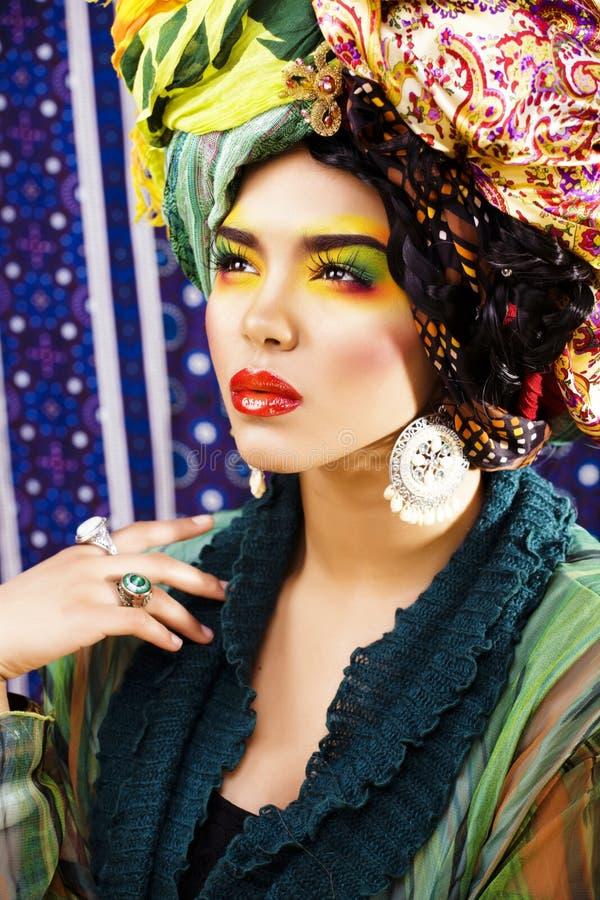 La donna intelligente di bellezza con creativo compone, molti scialli sulla testa come cubian, primo piano di sguardo di ethno fotografia stock