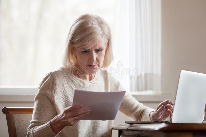 La donna invecchiata mezzo frustrata seria si è disturbata con la fattura domestica immagini stock