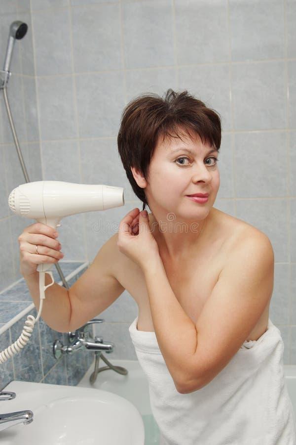 La donna invecchiata mezzo piacevole asciuga i suoi capelli con il hairdryer fotografia stock