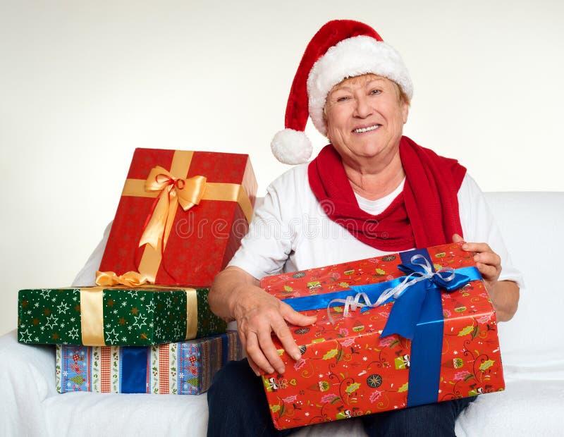 La donna invecchiata si è vestita in Santa che il cappello con i contenitori di regalo si siede sul sofà, fondo bianco Concetto d fotografia stock