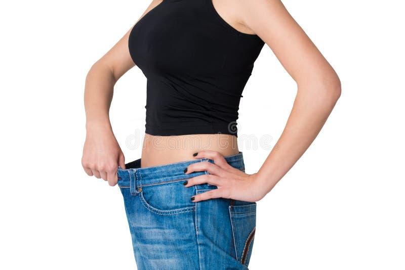 La donna isolata ha perso il peso ed i suoi pantaloni sono stile di vita troppo grande e sano fotografia stock
