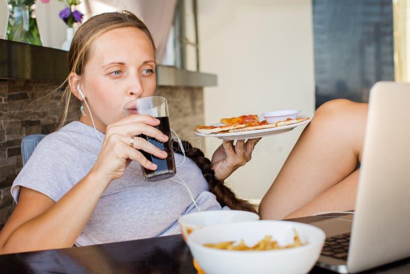 La donna lavora al computer ed a mangiare gli alimenti a rapida preparazione Vita non sana fotografia stock libera da diritti