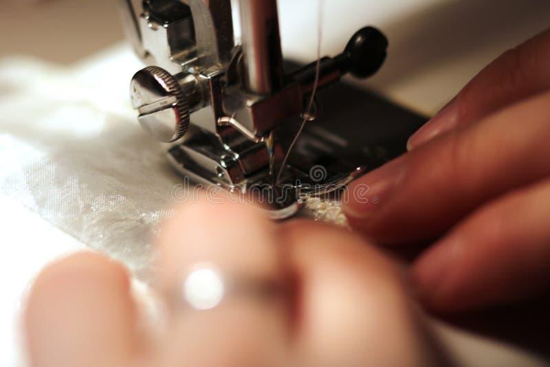 La donna lavora alla macchina per cucire immagini stock