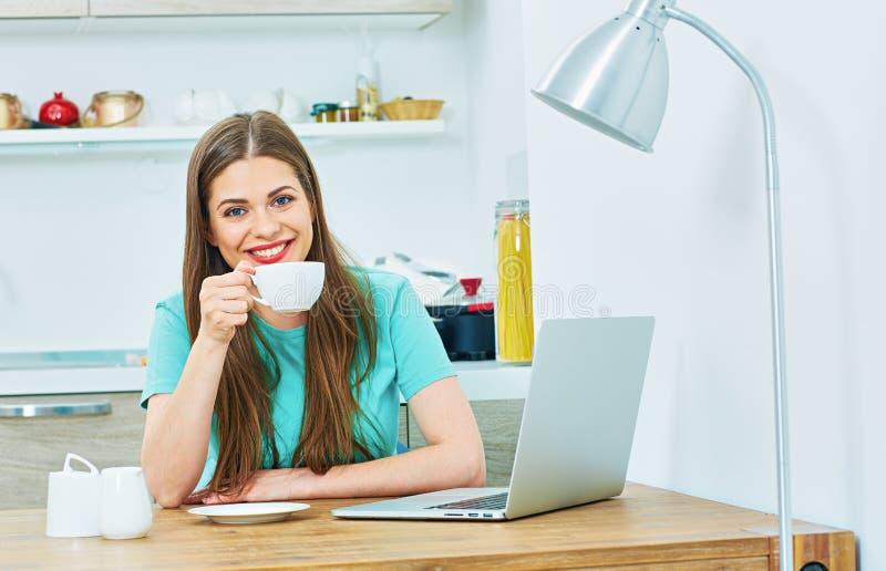 La donna lavora a casa la cucina con il computer portatile immagine stock libera da diritti