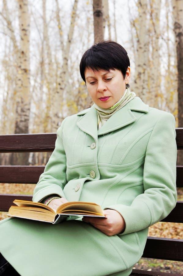 La donna legge il libro nella sosta di autunno fotografie stock libere da diritti