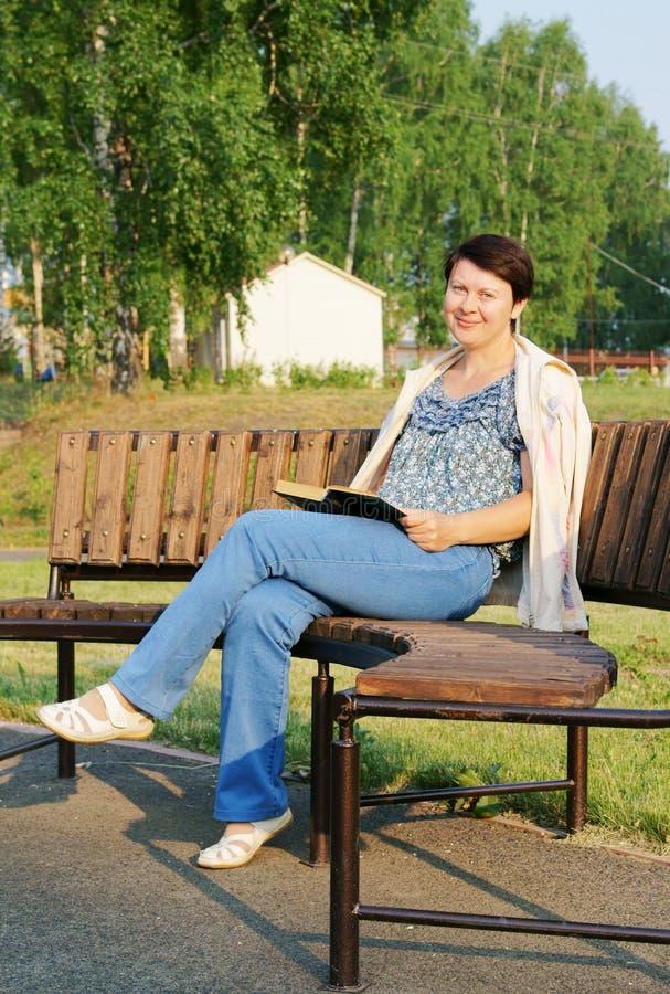 La donna legge un libro su un banco nella sosta fotografie stock