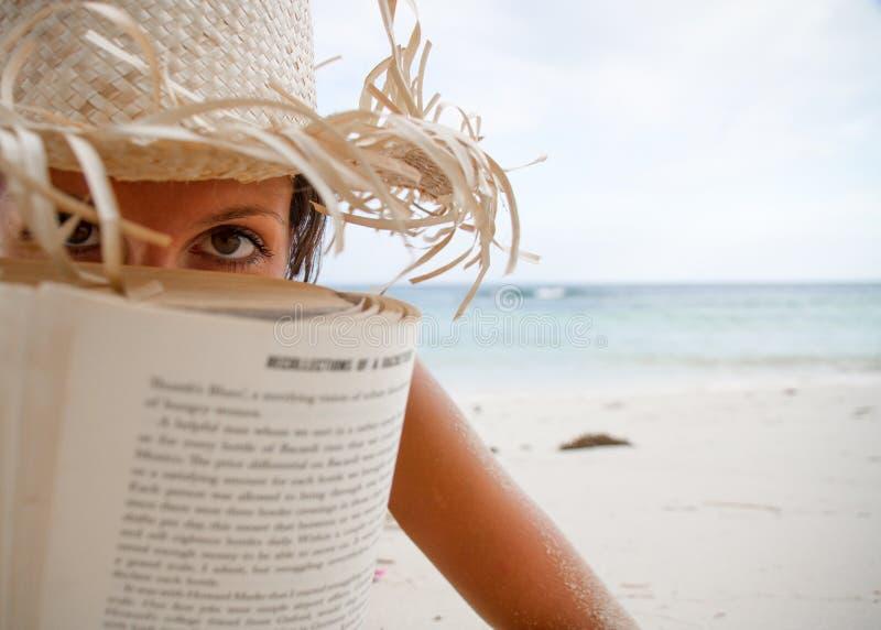 La donna legge un libro sulla spiaggia immagini stock