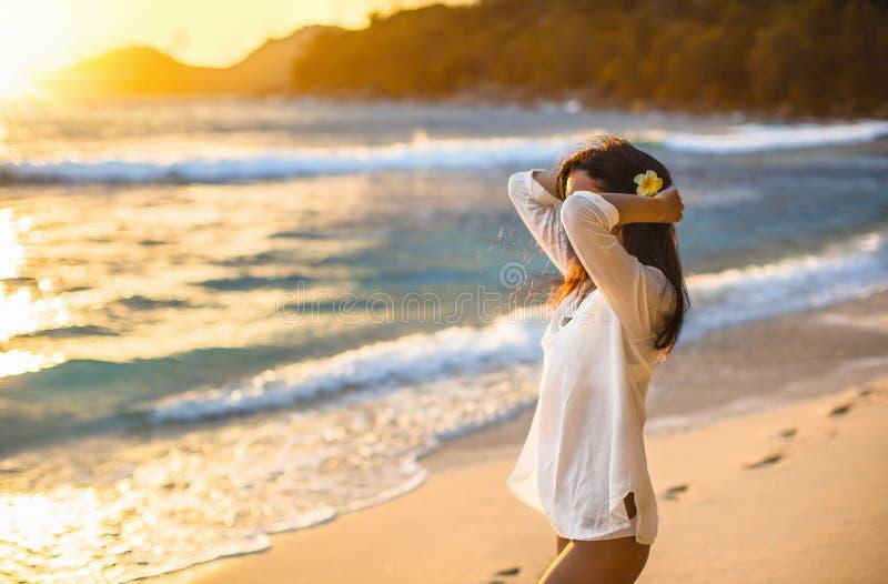 La donna libera gode della brezza dell'oceano al tramonto fotografie stock