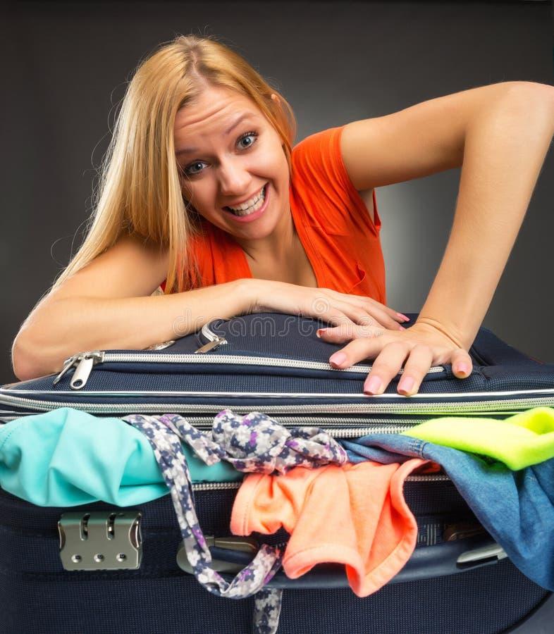 La donna lotta per chiudere una valigia piena fotografia stock libera da diritti