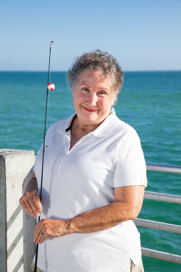 La donna maggiore ama pescare immagini stock