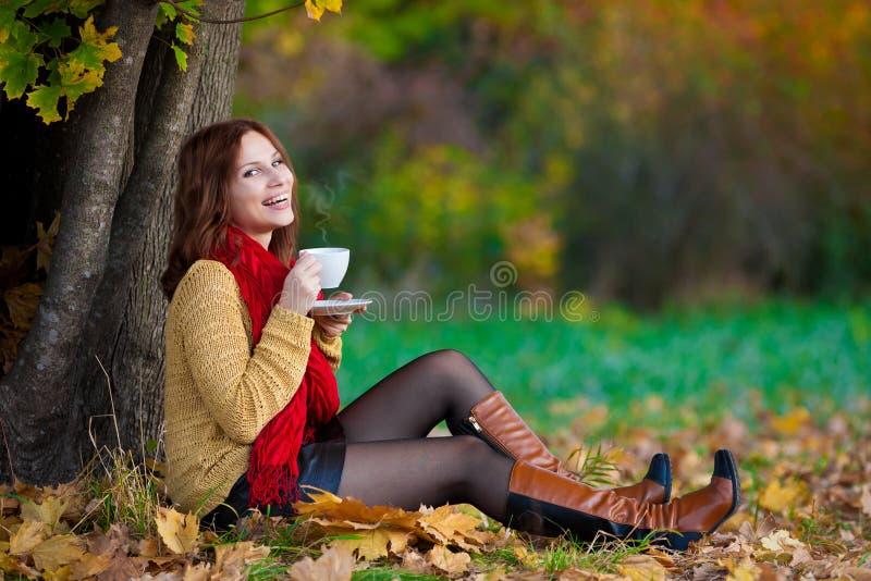 La donna in maglione beige e la sciarpa rossa bevono il tè fotografia stock