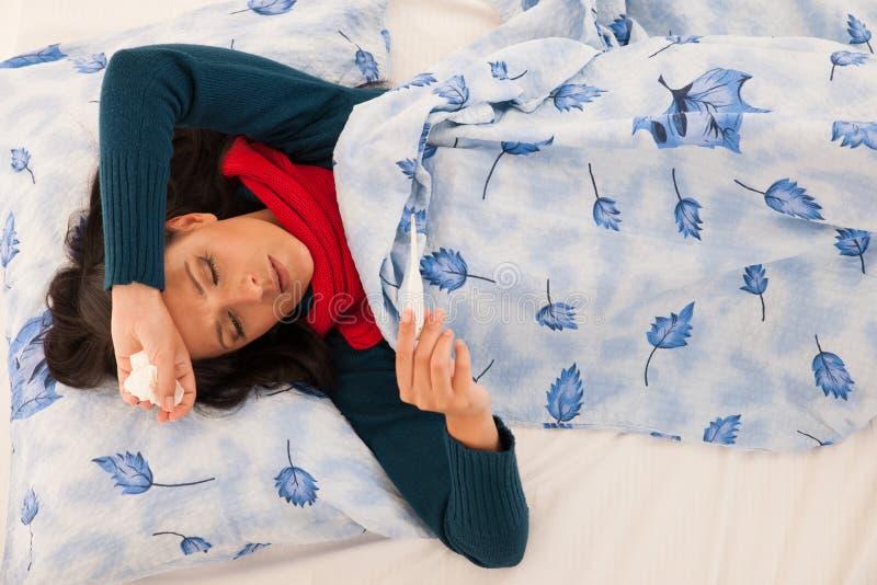 La donna malata ha febbre che controlla la temperatura corporea con il termometro i fotografia stock libera da diritti