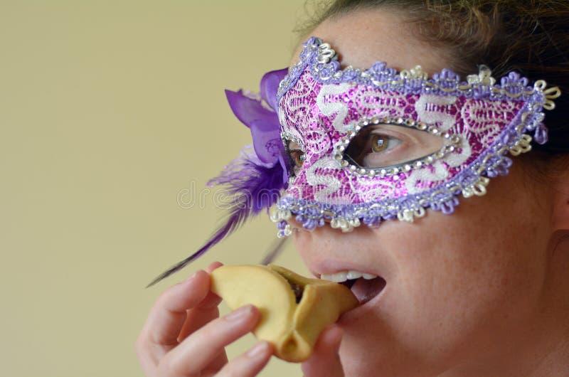 La donna mangia il biscotto di Hamantaschen e la maschera d'uso di Purim immagini stock