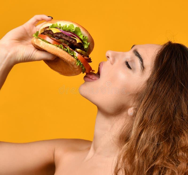 La donna mangia il panino dell'hamburger con la bocca affamata su fondo giallo fotografia stock