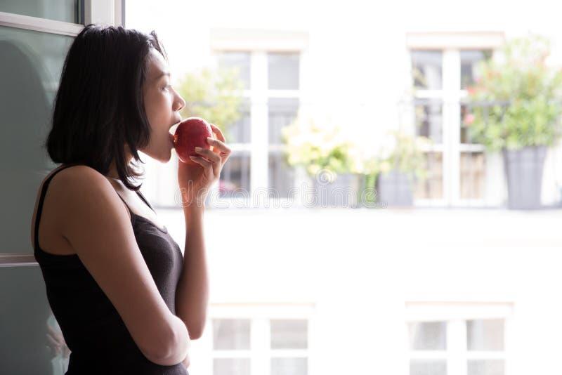 La donna mangia la mela fotografia stock