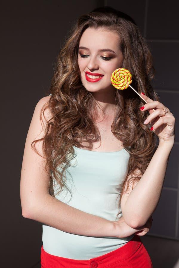 La donna mangia la lecca-lecca dolce della caramella fotografia stock libera da diritti